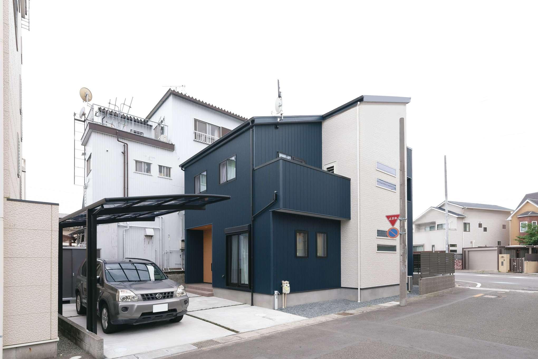 外壁はブルーのガルバリウムとサイディングのツートン。片流れの屋根と横スリット窓が外観のアクセントに