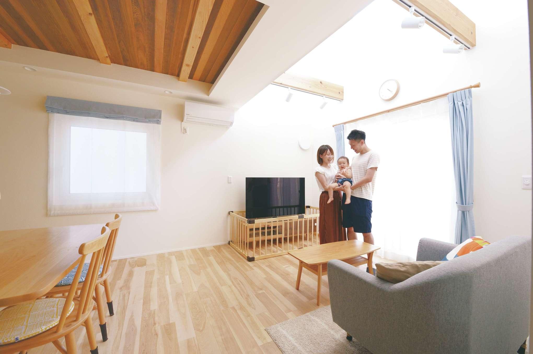 低燃費住宅 静岡(TK武田建築)【子育て、自然素材、省エネ】吹き抜けにある窓から光が降り注ぐLDK。シーリングファンを伝って風が抜け、ここにいるとまるで家が呼吸しているかのような心地よさ。壁や天井は調湿効果のある漆喰で仕上げ、カビの心配もなし。外断熱と内断熱のハイブリッド断熱により、壁内に結露が発生しないので家が長持ちする。ダイニングの天井の一部にはウェスタンレッドシダーを施し、夜には間接照明が落ち着いた雰囲気を演出する。裸足でも気持ち良く過ごせるよう床材に無垢のカバザクラを採用