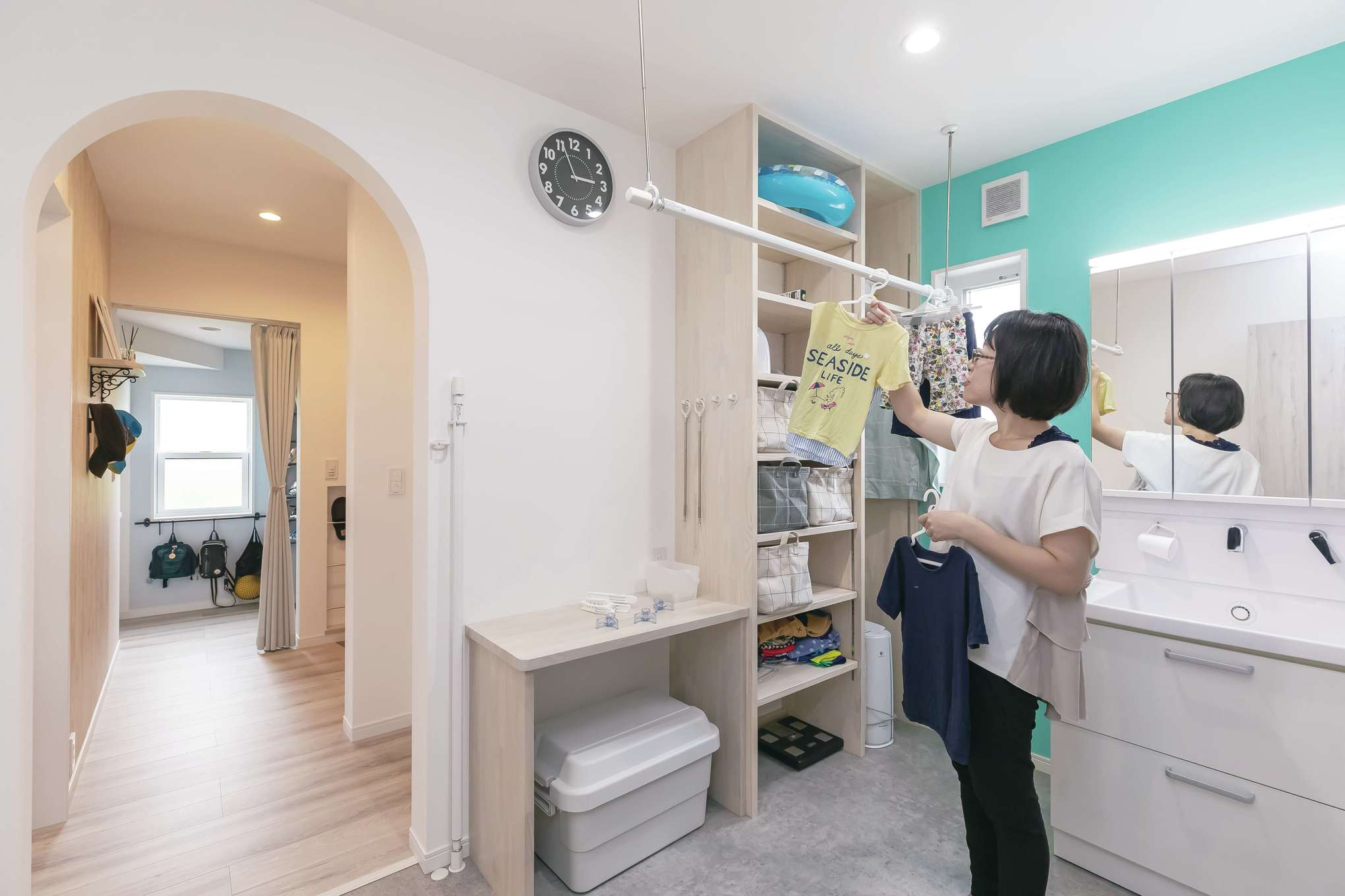 原田工務店【デザイン住宅、子育て、間取り】ティファニーブルーのクロスが映える洗面コーナーには室内干しや収納棚を設けてあり、「洗う・干す・しまう」が一か所でできる。玄関からの動線も便利
