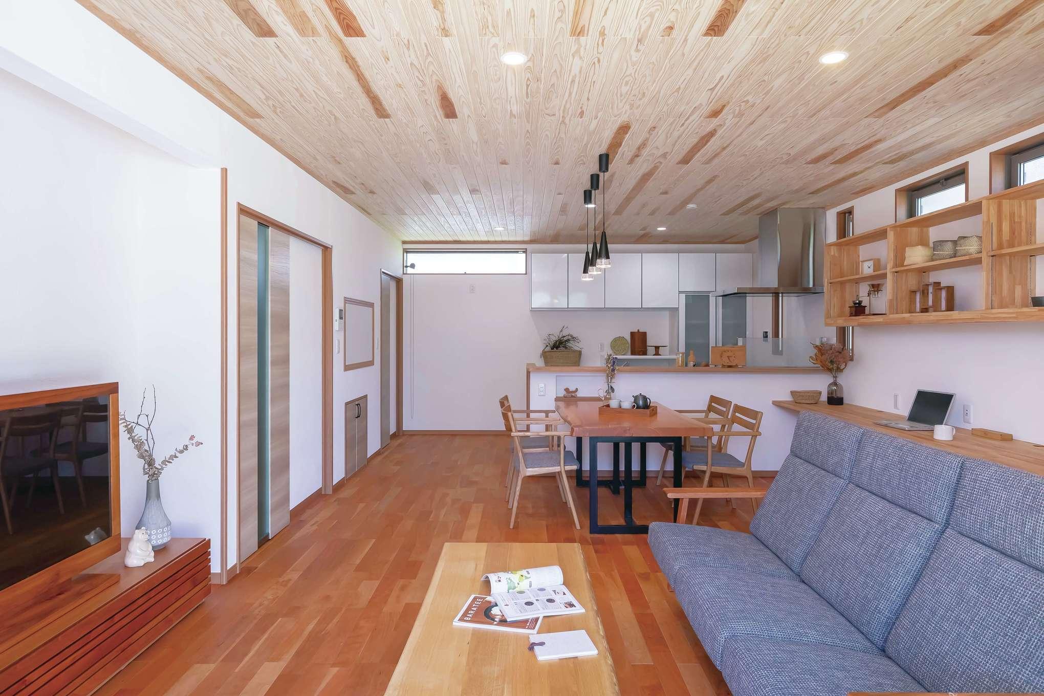 住まいるコーポレーション【デザイン住宅、自然素材、間取り】ブラックチェリーの床のシックな色目がLDK全体に落ち着いた雰囲気をもたらしている。天井も無垢板張りで、壁には珪藻土を使用。自然素材の空間に心が癒される