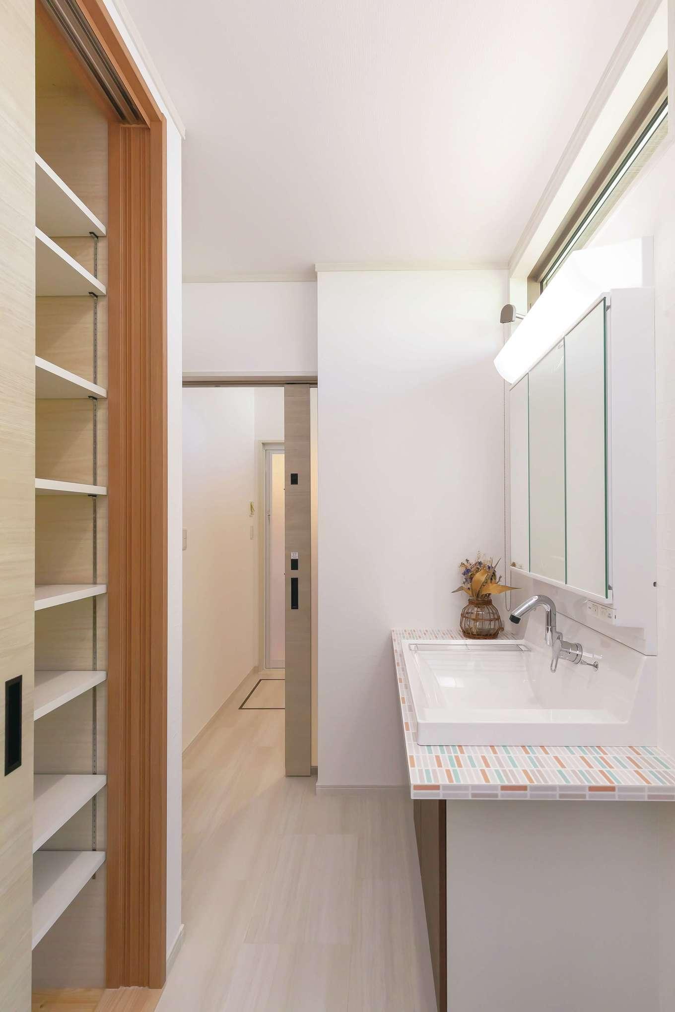 住まいるコーポレーション【デザイン住宅、自然素材、間取り】背面に大きな収納がある洗面スペースは、玄関からキッチンへ通り抜けられる場所に配置。勝手口もあり、移動がラクラク