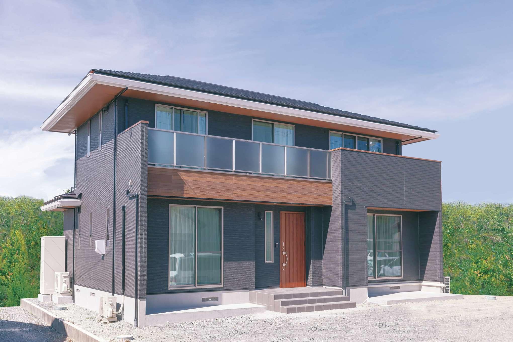 住まいるコーポレーション【デザイン住宅、自然素材、間取り】濃いグレーの外壁に木目が映える外観。玄関ポーチの階段を幅広くとり、格調高い雰囲気に