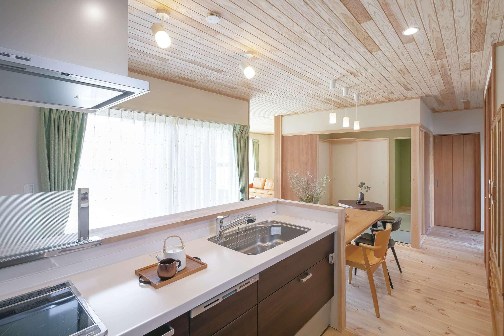 住まいるコーポレーション【デザイン住宅、和風、自然素材】ワークスペースを広々と確保した機能的な対面キッチンはテーブルを一列に配置。正面に窓があるので、庭を眺めながらいつも気持ちよく料理ができそう