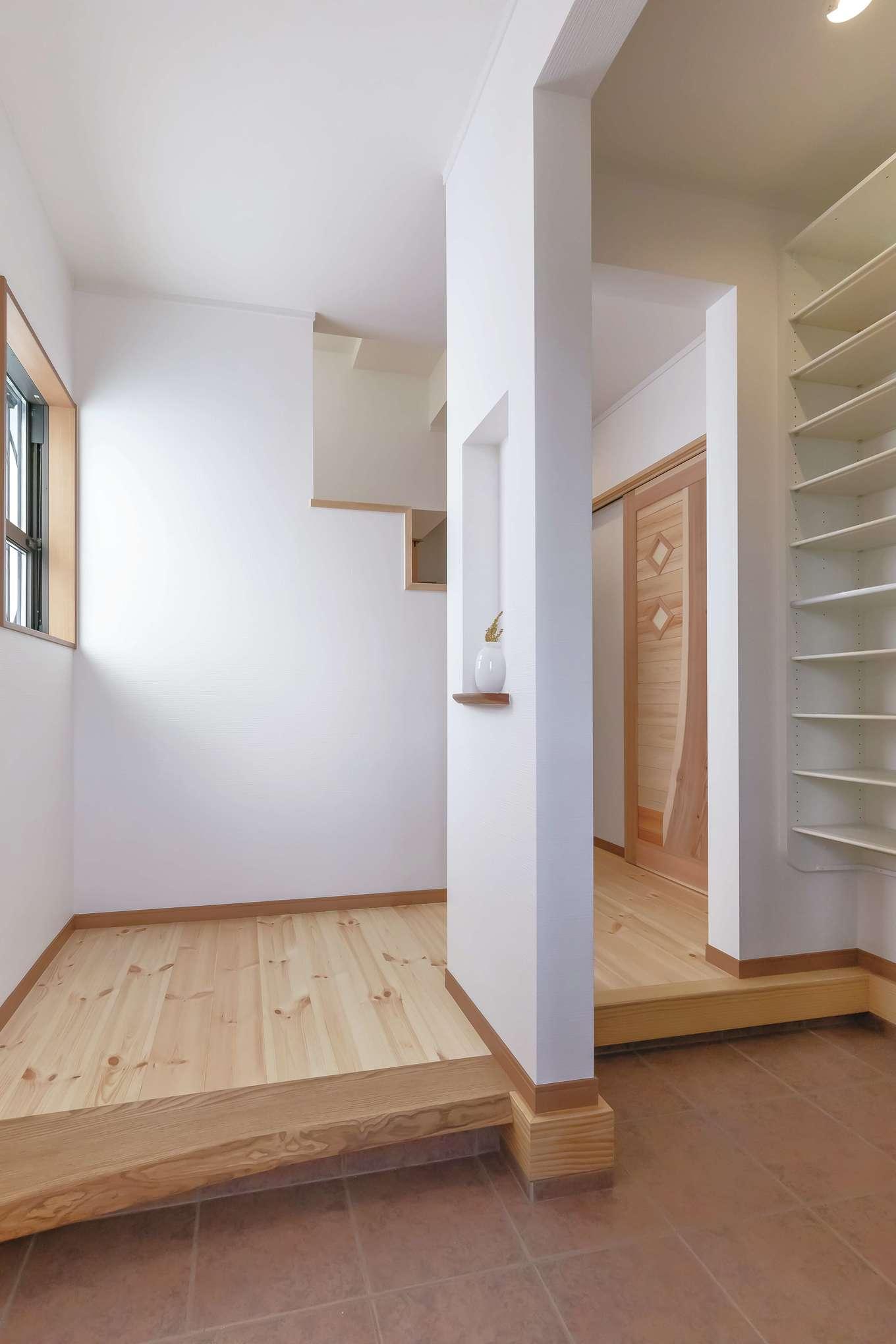 住まいるコーポレーション【デザイン住宅、和風、自然素材】玄関にはシューズクロークと家族用の下足スペースを確保。上り框には高級な耳付きの無垢材を使用。壁のニッチには季節の花を飾って