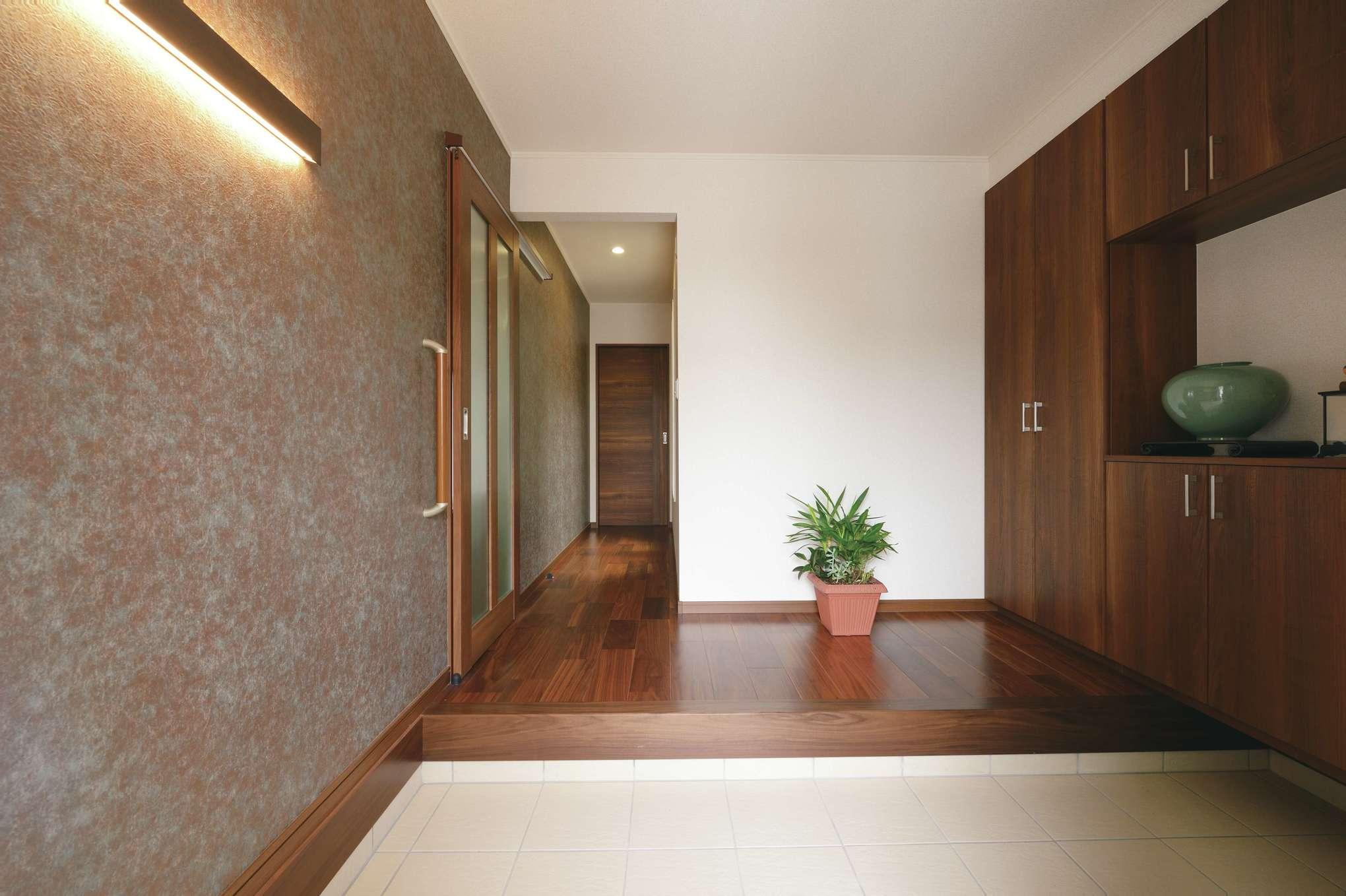 朝日住宅【デザイン住宅、夫婦で暮らす、平屋】玄関ホールから廊下へ続くグレーの壁紙は、革のような素材感がモダン。間接照明とのバランスもいい