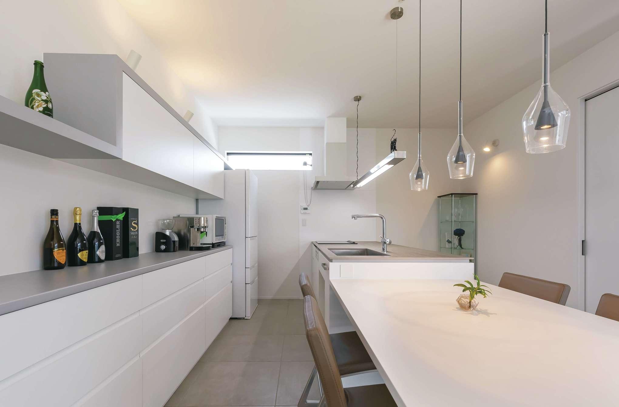 MABUCHI【デザイン住宅、省エネ、建築家】オーダーメイドのキッチンはテーブルと一体型。背面の収納は床のフロアタイルに合わせてグレーをアクセントに活かしている