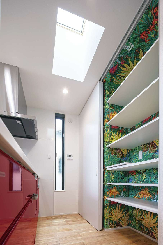 キッチンの真上にトップライトを設置。トイレと同じ華やかなクロスをパントリー内に採用。フェラーリレッドのキッチンが差し色に