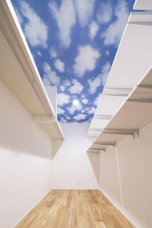 広くて細長いウォークインクローゼット。窓がない代わりに、天井に青空のクロスを貼って気分爽快♪