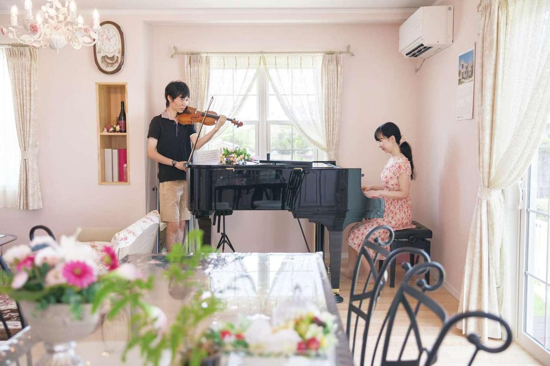 セルコホーム浜松(オバタケイ)【輸入住宅、趣味、ガレージ】リビングでピアノとバイオリンの二重奏を楽しむ夫妻。防音性が高いため、周囲に気兼ねなく演奏できる