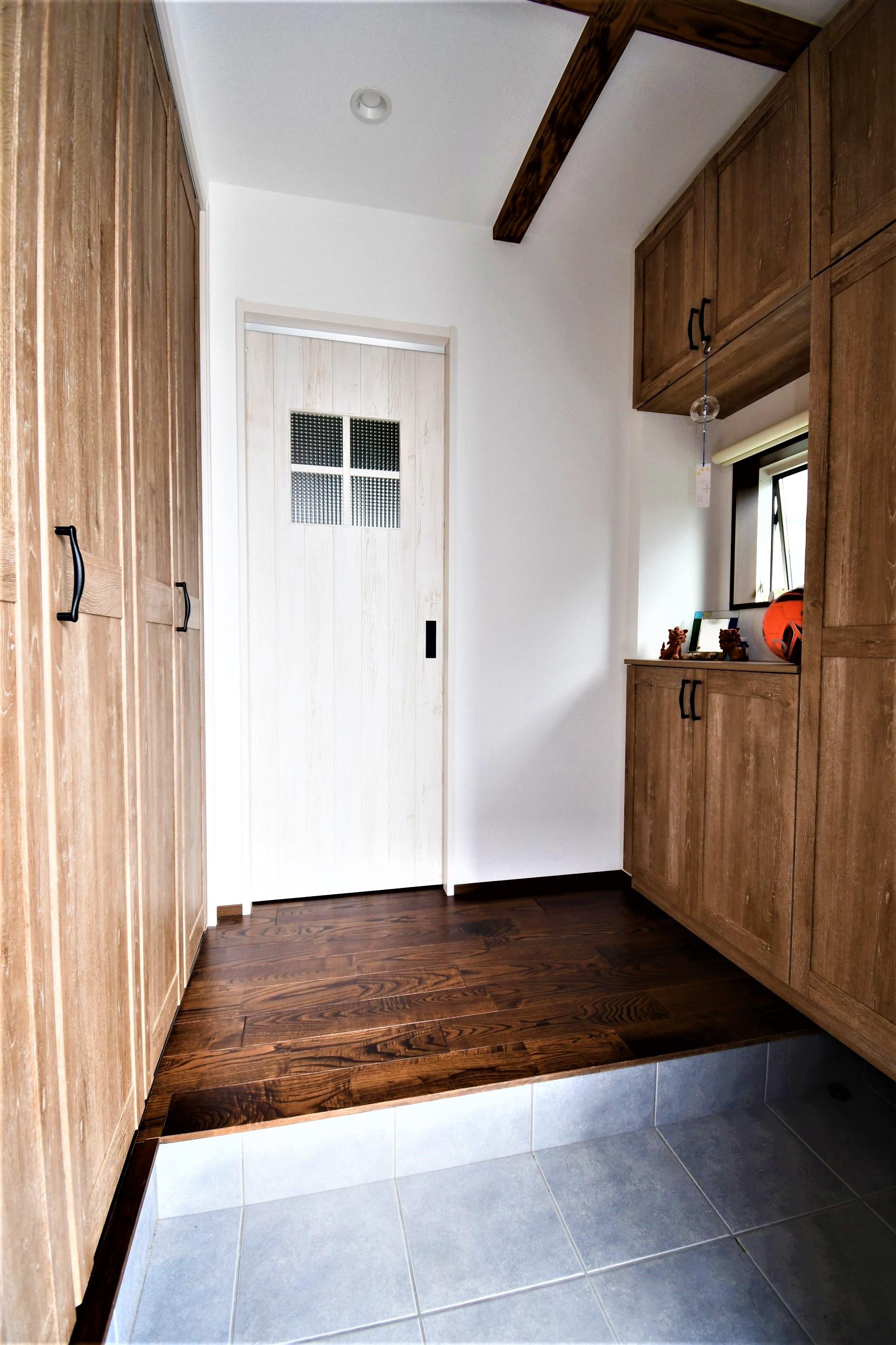 丸七建設興業【デザイン住宅、間取り、インテリア】収納豊富な玄関ホール。濃い木目が空間に彩を与えている