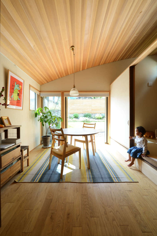 石牧建築【自然素材、狭小住宅、建築家】天井をRにしたことで、奥行きと開放感が生まれたダイニング。椅子に座ると、ちょうど目線と同じ高さに庭の花々が見える。クリ、杉、チェリー、ウォールナットなど、自社工場にストックしておいた多彩な樹種を適材適所に使用。ぽってりとした可愛らしいペンダントライトは、森町在住のガラス作家によるハンドメイド作品
