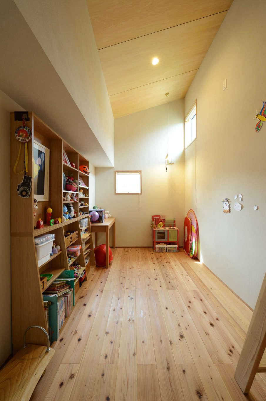 石牧建築【自然素材、狭小住宅、建築家】天井の低い2階の廊下から一歩中に入ると、高い天井が広がる長女の部屋。調湿効果にすぐれた、あたたかい肌触りの無垢の木の家で過ごす子どもは、おだやかな性格の良い子に育ちそう