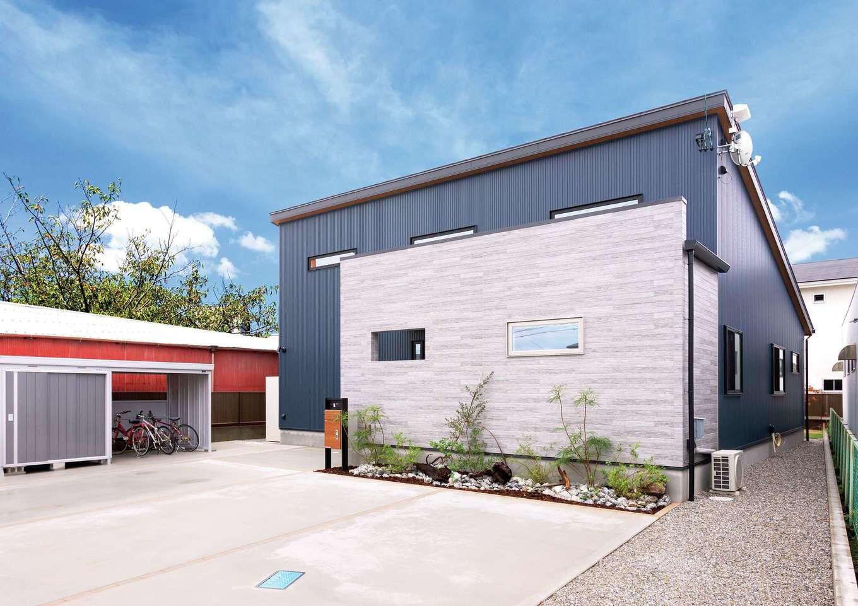 Yamaguchi Design 【省エネ、間取り、平屋】一見、平屋とは思えないほどのスケール感がある外観。交通量の多い北面道路を考慮して、グレーのガルバリウムにサイディングを組み合わせ、ポーチと玄関をやわらかく目隠しした。片流れの屋根に18kWの太陽光発電を搭載