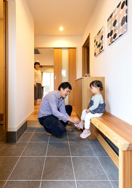 土間仕上げの玄関ホール。大工さん手づくりの木のベンチは、子どもも祖母も靴を履きやすくて大助かり。左側に家族専用のシューズクロークを設け、玄関は常にスッキリと