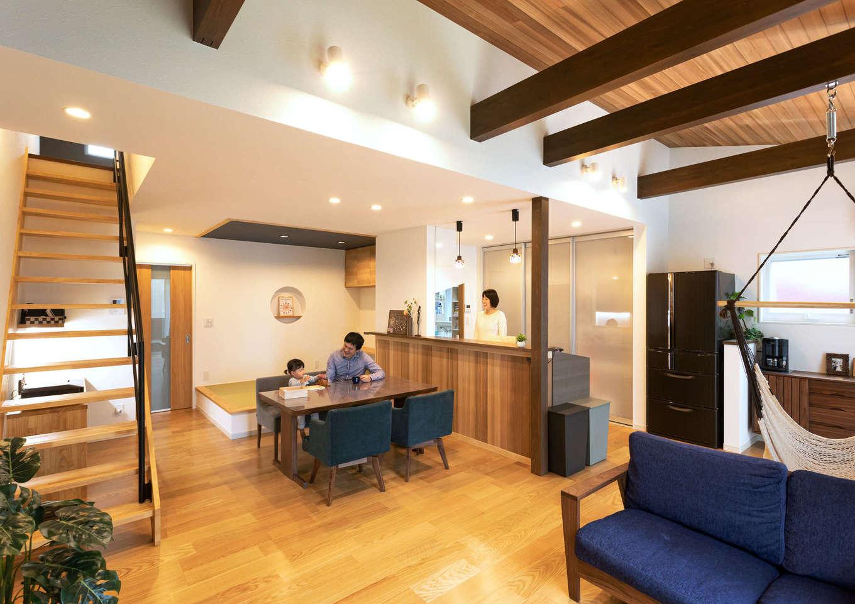 Yamaguchi Design 【省エネ、間取り、平屋】ワンフロアでつながりを持たせながら、リビングを勾配天井にしたり、天井とキッチンの腰壁に米杉を張るなど、空間に変化をもたせたLDK。ご主人のたっての希望で、梁にハンモックを吊り下げた