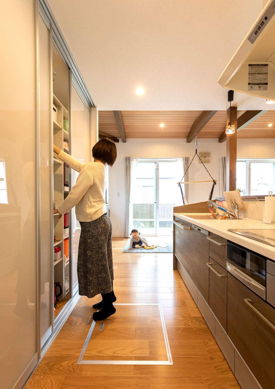 家事をしながら子どもの様子が見える位置にキッチンをレイアウト。おしゃれな空間に生活感を出さないよう、半透明の引き戸で調理家電や食器を隠せる。ランドリールームからウッドデッキまで一直線につながる動線が共働き・子育て奥さまの家事時間を短縮
