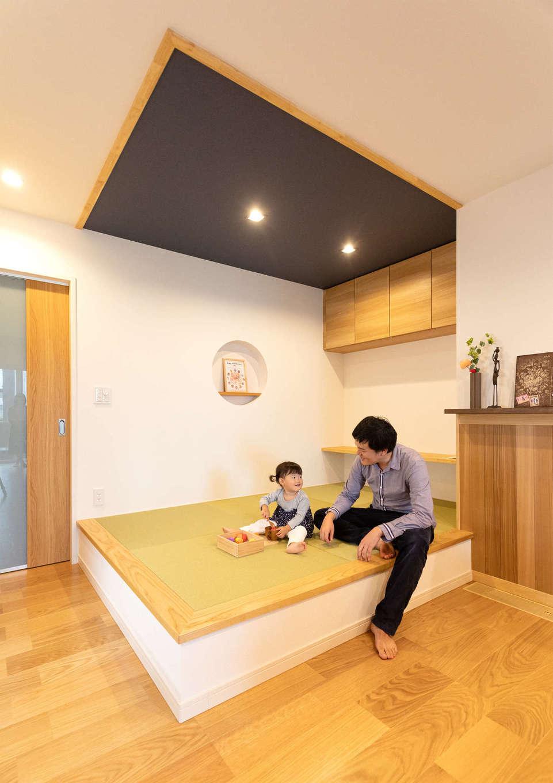 Yamaguchi Design 【省エネ、間取り、平屋】リビングの一角にしつらえた小上がりの畳コーナー。子どもと遊んだり、ご主人がゴロンと横になったり、ゲストが椅子代わりに使ったりと大活躍。まあるく切ったニッチと天井のクロスがアクセントに
