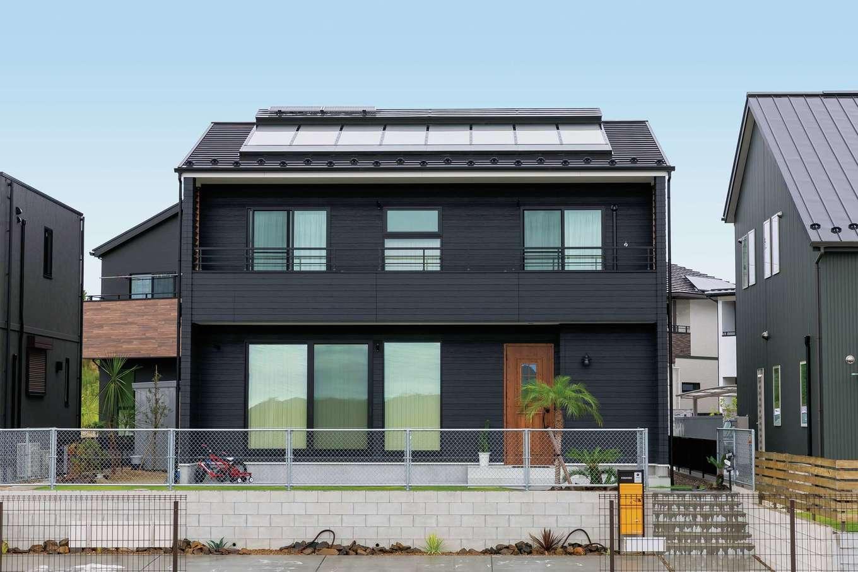 ソーラーホーム/OMソーラーの家【デザイン住宅、省エネ、間取り】分譲地でひときわ目をひくマットブラックの外観デザイン。アメリカンフェンスと椰子の木がリゾート感を演出。屋根に降り注ぐ太陽の熱で空気を暖め、それを床下に送り、基礎コンクリートに熱を蓄え、床面の吹き出し口から暖められた空気を室内に循環させるOMソーラーシステムを採用。家全体を足元からじんわりと柔らかい暖かさで包み込む
