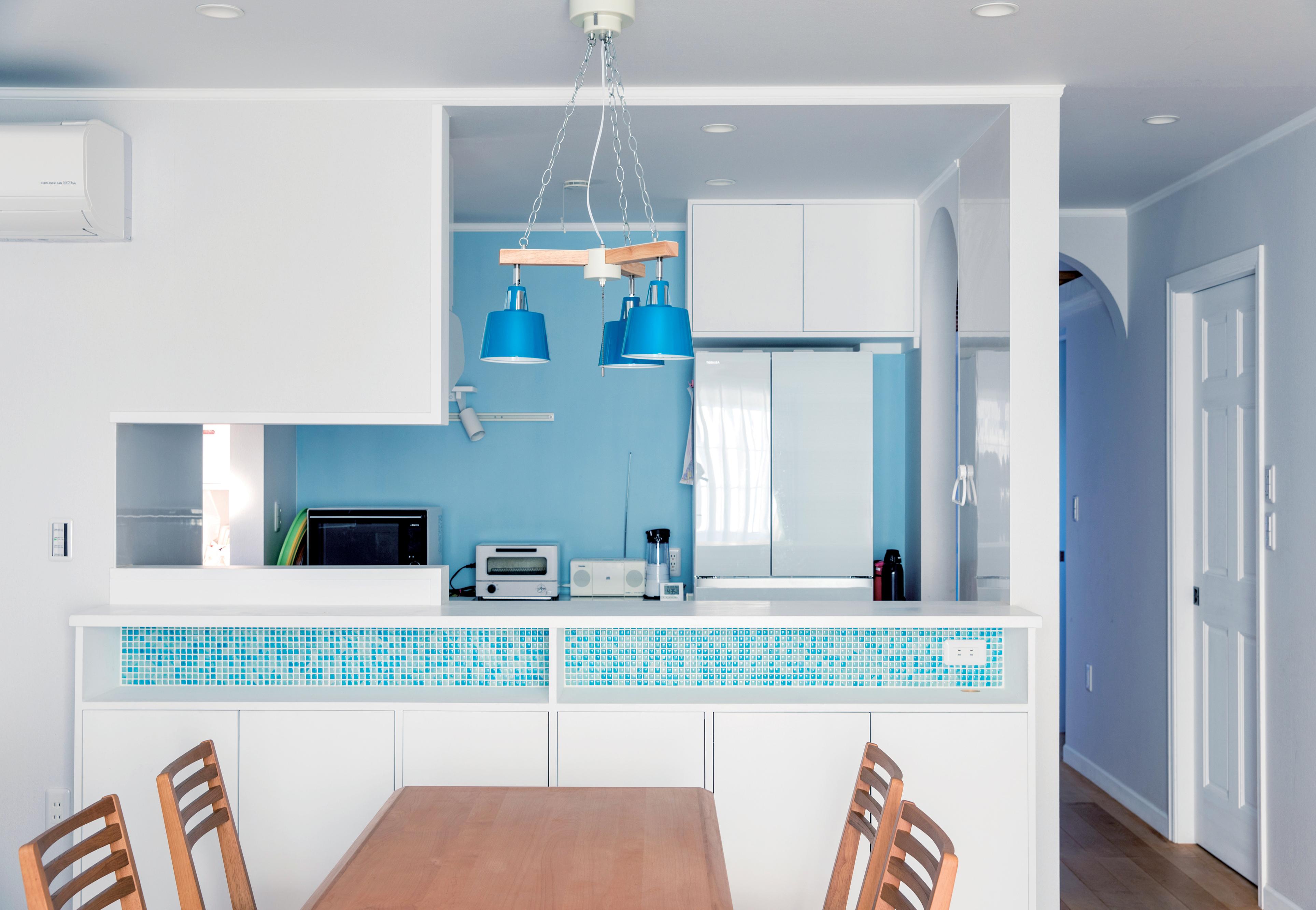 スカイグラウンド【デザイン住宅、子育て、趣味】白と青を基調にしたキッチンからすべり台で遊ぶ子どもを見守る