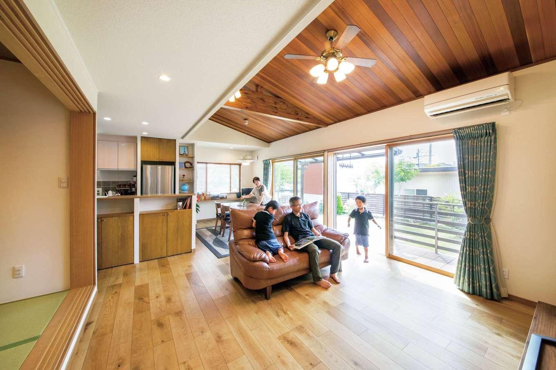 オカダ【子育て、自然素材、間取り】和室と合わせると27.5畳のLDK。レッドシダーの勾配天井採用し、より開放的な雰囲気に。大きな窓を開けるとウッドデッキ、広い庭へとつながり、子どもたちが外と中を自由に行き来する