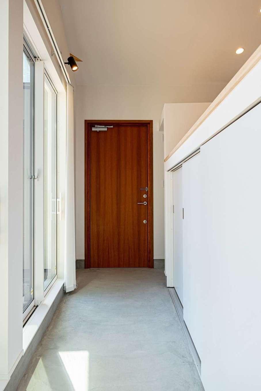 無垢の玄関ドアを開けると、掃き出し窓に沿って広い土間廊下が続き、行き止まりがダイニングキッチン。白い腰壁の反対側にリビングがある
