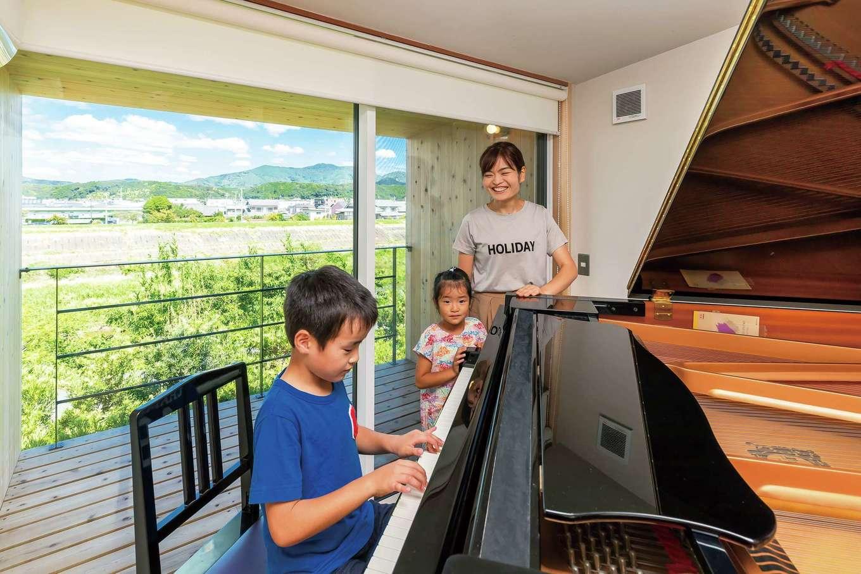 石牧建築【デザイン住宅、和風、趣味】大きな窓に都田川と豊かな緑の絶景が広がる2階のピアノ室。家族でピアノを弾いたり歌を歌ったりと、家事・育児の合間にほっとくつろげる憩いの空間でもある