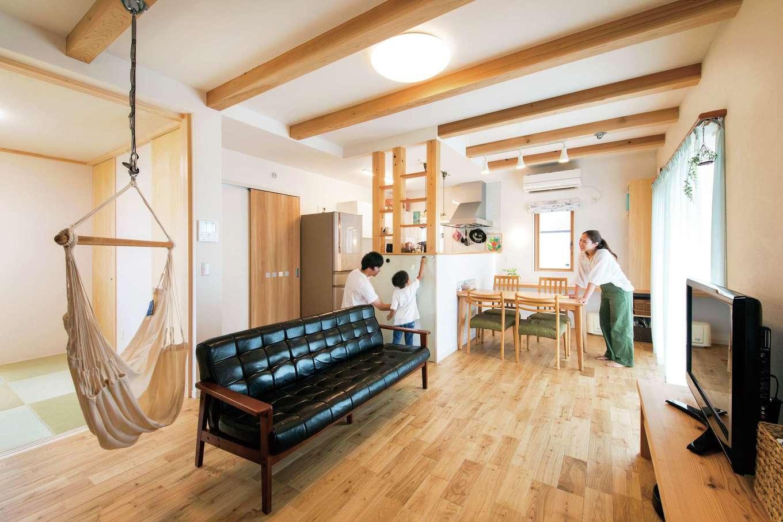 水田建設【子育て、自然素材、省エネ】LDKと続き間の和室。キッチン横の構造上必要な柱の間に棚を付けオープンラックにして、収納を確保するなど、奥さまのアイデアが随所に光る