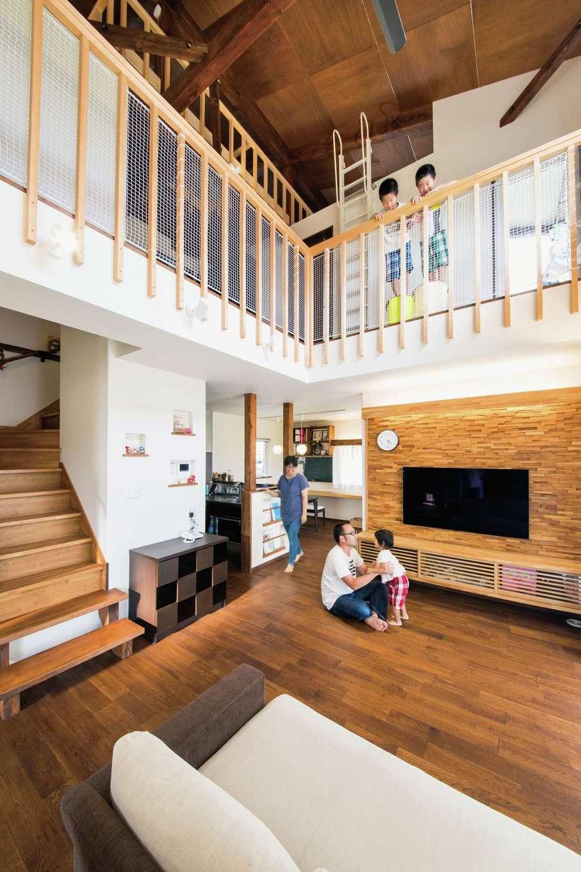 梅村建築【子育て、収納力、自然素材】家族がどこにいても気配がわかる吹き抜けのリビング。これほどの大空間でも超高気密・高断熱性能で家中の温度差が少ない。キッチンとダイニングがリビングから丸見えにならないようにしたのもこだわり。あたたかな木のぬくもりとホワイトの壁でさらにゆったりとした空間に