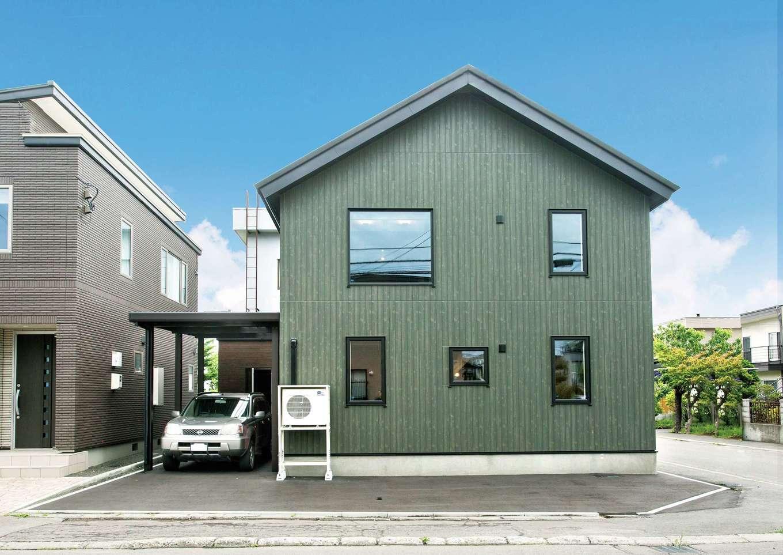 サイエンスホーム【デザイン住宅、趣味、自然素材】三角屋根のシンプルな外観フォルム。夫婦の好きな深いグリーン系のサイディングにブラックの窓枠が映える
