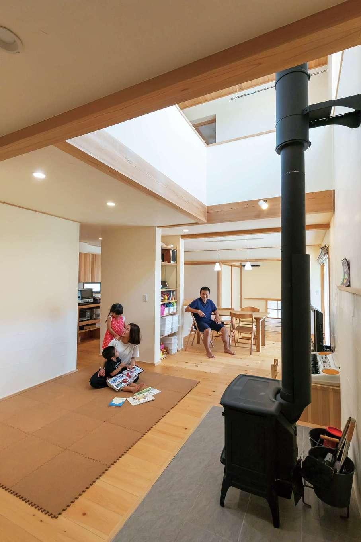 ナルセノイエ【子育て、和風、自然素材】無垢の木と漆喰塗りの壁や天井が心地いい1階。薪ストーブのある吹き抜けのリビングからダイニング、和室までを段差なく繋げたことで、実際の面積以上に広がりを感じられる