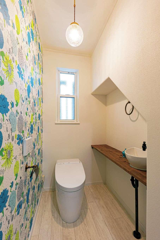 1階トイレは階段下のスペースを利用し、個室内に手洗いカウンターを造作。アクセントクロスは奥さまチョイス