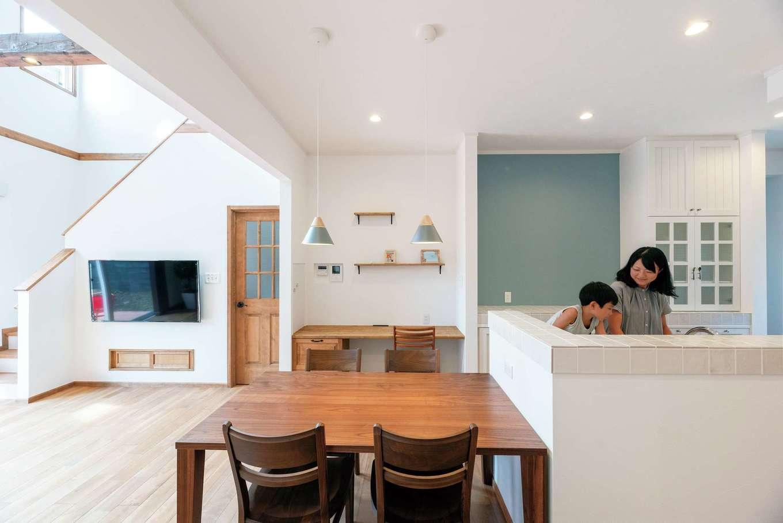 ハートホーム【輸入住宅、自然素材、ガレージ】ウッディでナチュラルなLDK。キッチン背面のスモーキーグレーのクロスで北欧テイストに。テレビ下の小さな引き戸にはDVDプレーヤーを収納