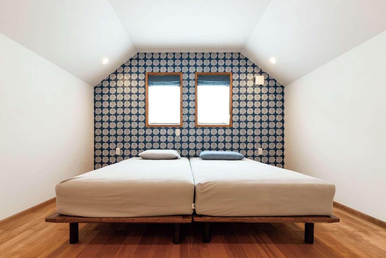 ハートホーム【輸入住宅、自然素材、ガレージ】屋根の勾配を活かした寝室。ふたつ並んだ窓は、外観デザインを重視してシンメトリーに。アクセントクロスは、奥さまの好きなマリメッコを用意して施工してもらった