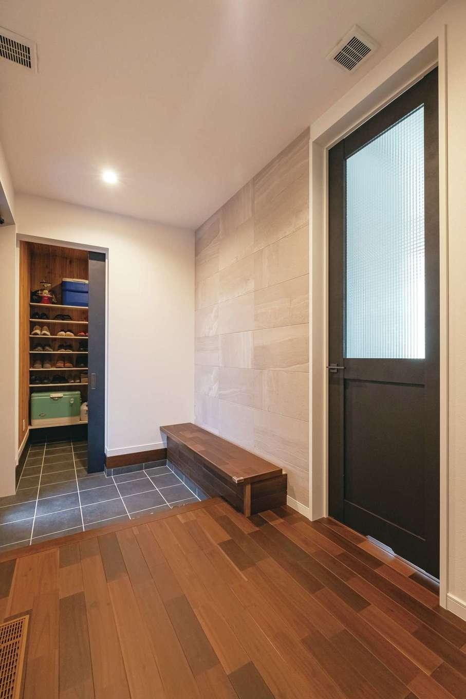 たっぷりのシューズクロークを備えた玄関。ベンチの下も収納になっている。正面の壁には調湿、脱臭機能をもつエコカラットを採用