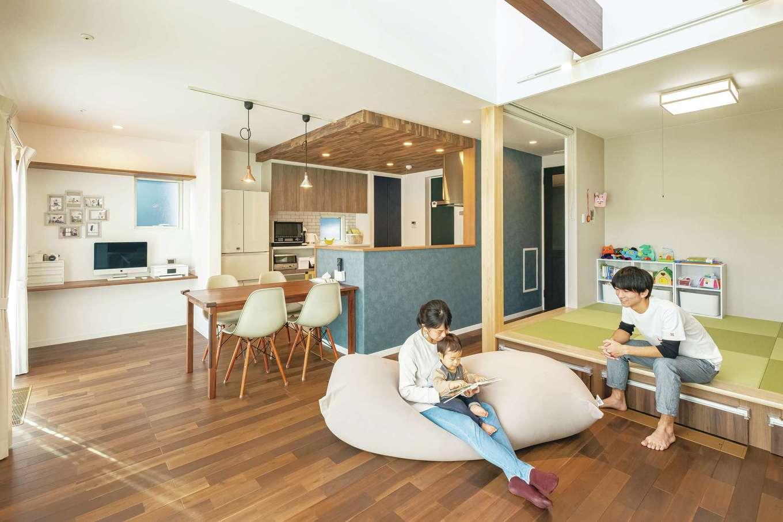 大らかな空間だが段差や素材で役割がわけられ、居心地がいい。畳の下の収納は赤ちゃんグッズ入れに重宝