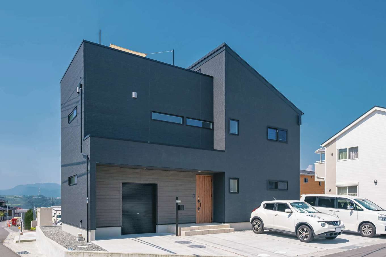 黒い外壁がスタイリッシュなK邸。木目の玄関ドアが、訪れる人を自然に誘う