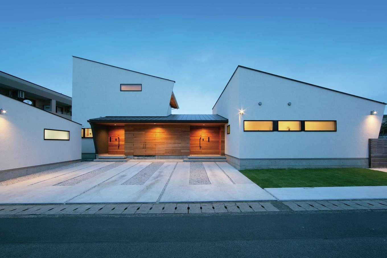 両翼を開いたような美しいプロポーション。二世帯をつなぐ部分を大きなエントランスに見立て、ドアと壁が一体化したデザインになるよう、チーク材の壁をアクセントとして採用した。バイクガレージの扉も溶け込んでいる