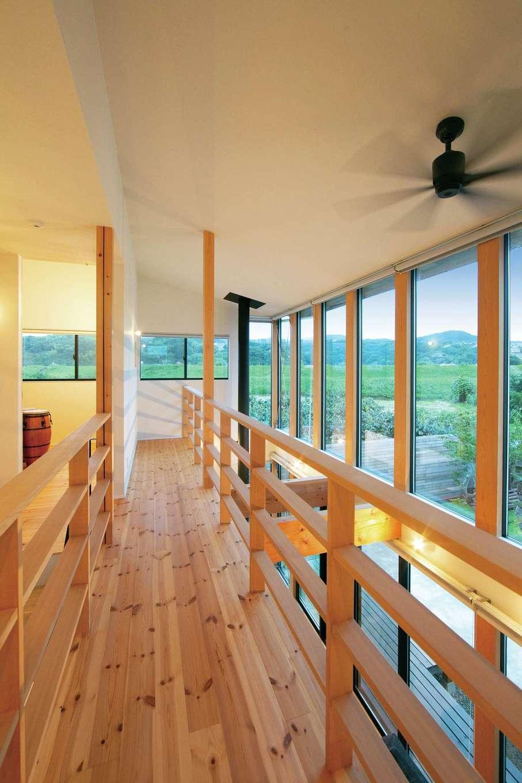空中桟橋のような渡り廊下。狩野川の借景を楽しめるよう大きな窓を採用した。深い軒が強い陽射しを遮る