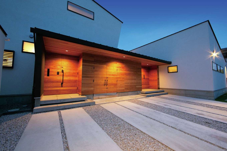 TENアーキテクツ 一級建築士事務所【二世帯住宅、高級住宅、建築家】道行く人が思わず二度見していく、建築家住宅らしい斬新なファサード。2つの玄関ドアに挟まれた中央部分はバイクガレージ