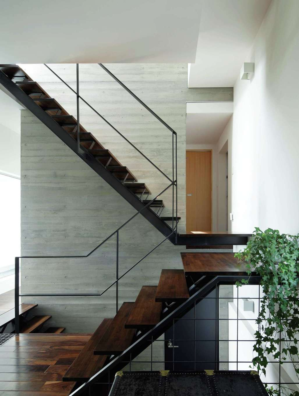 久保田建設【高級住宅、建築家、鉄骨鉄筋コンクリート構造】玄関ホールの中央に、コンクリートの厚い壁が3層に渡って伸びる。それに寄り添うように木と鉄で構成された階段から全スペースが立体的につながっている