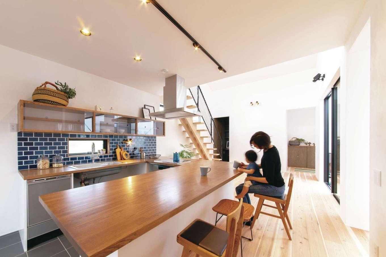 ソラマド静岡(オネストホーム)【子育て、デザイン住宅、間取り】ソラマドキッチンはカスタマイズも自由自在。吊り戸棚の下は、ダークカラーのタイルを用いてアクセントに。ダイニングテーブルを兼ねているので、配膳や後片付けも楽々
