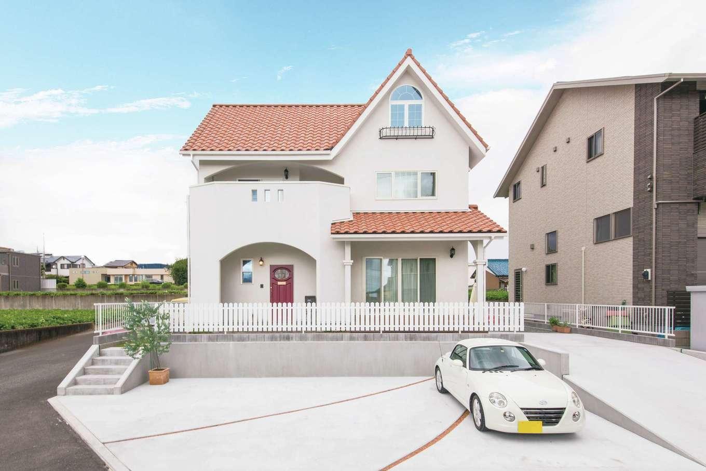 富士ホームズデザイン【デザイン住宅、子育て、インテリア】奥さまの子どもの頃からの夢を叶えたプロヴァンススタイルの外観。緑豊かなロケーションで、オレンジの瓦と白い壁が青い空にくっきりと映える。駐車場脇をスロープにしたことで、ゲストの車も多く停められるし、老後の暮らしも安心