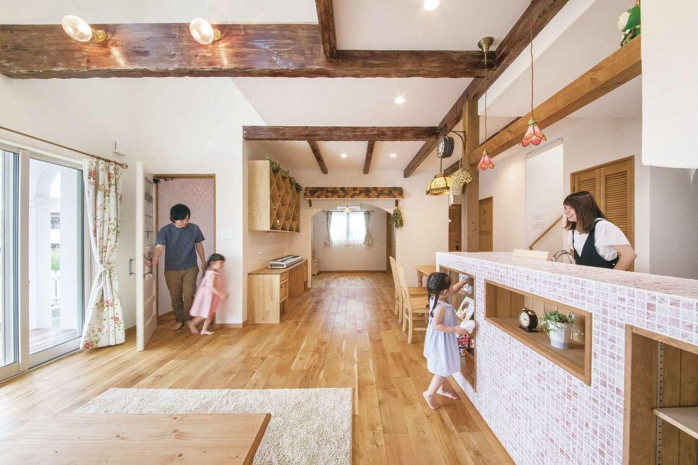 富士ホームズデザイン【デザイン住宅、子育て、インテリア】開放感あふれる吹抜けのLDK。淡いピンクのタイルを貼ったキッチンがインテリアの主役に。上総さん自ら太い梁にエイジング加工を施した。ダイニングテーブルのペンダントライトは英国製のアンティークランプ