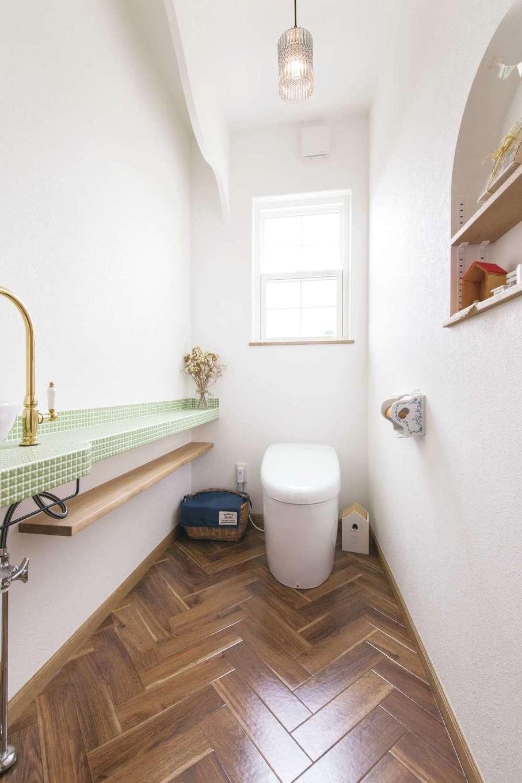 富士ホームズデザイン【デザイン住宅、子育て、インテリア】ヘリンボーン張りの床を採用したトイレ。タイル、水栓、照明、Rのニッチなど、落ち着いた空間の中にたくさんのこだわりが凝縮されている