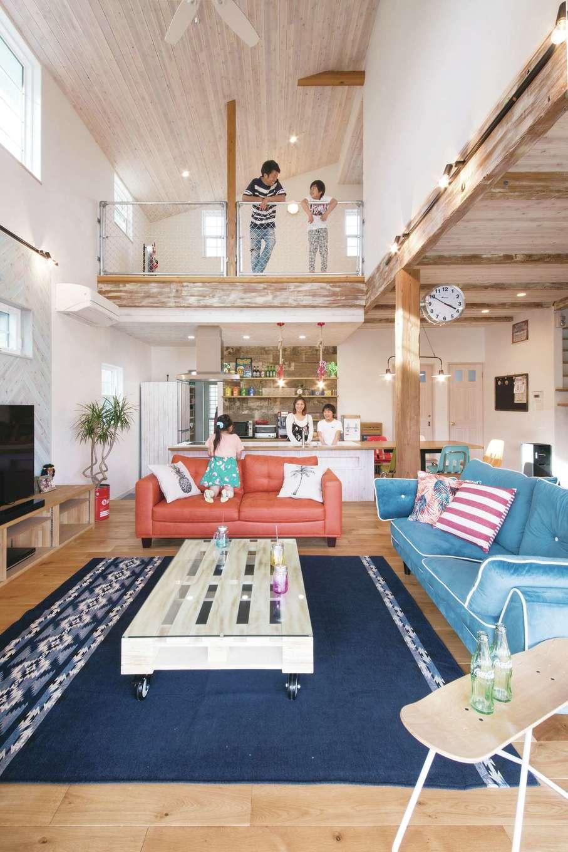 富士ホームズデザイン【デザイン住宅、子育て、インテリア】ダイナミックな吹抜けのリビング。キッチンでは家族がどこにいても気配を感じられる。社長と上総さんが塗装した現しの梁がシャビーシックな雰囲気を演出