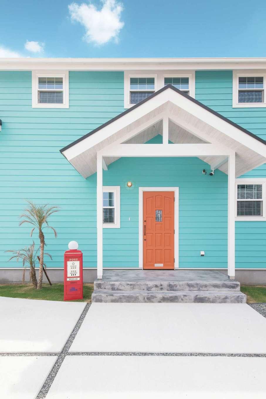 富士ホームズデザイン【デザイン住宅、子育て、インテリア】ブルー&ホワイトにオレンジ色のドアがポップな玄関。かわいらしいポストとパームツリーがお出迎え