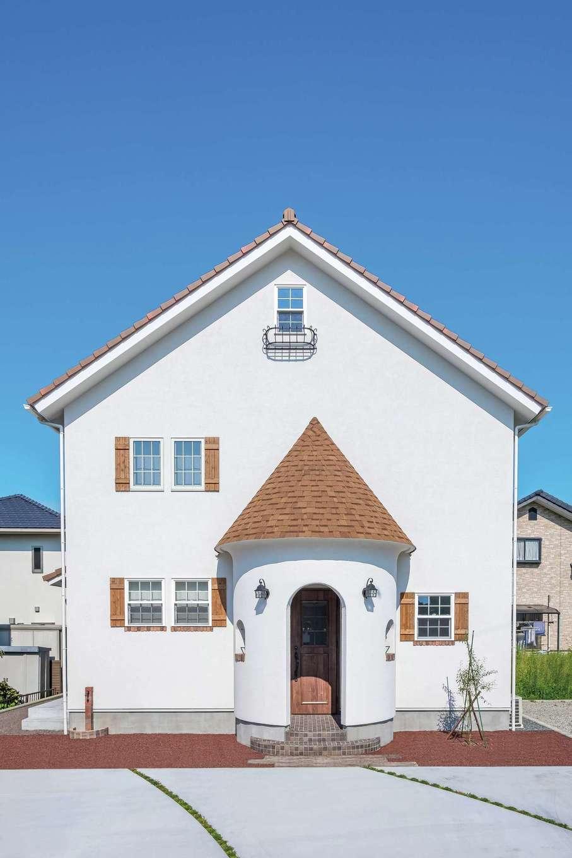 富士ホームズデザイン【デザイン住宅、輸入住宅、インテリア】塗り壁の外観は、とんがり屋根がアクセント。格子窓と鎧戸もほどよい個性を生んでいる。半円形のポーチに設けられた小窓はアイアンとレンガでデコレートされるなど、細部まで手抜かりなし