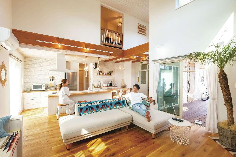 富士ホームズデザイン【デザイン住宅、輸入住宅、インテリア】カバードポーチや2階空間ともつながり、圧倒的な開放感で満たされるLDK。床のオークによって落ち着きとリゾート感が溶け込み、心からリラックスして過ごすことができる。雰囲気のみならず、上総さんによる女性目線の配慮も魅力。回遊できるキッチンの奥には抜群の収納力を誇るウォークインのほか、機能的なパントリーや室内干し可能なランドリールームが用意され、家事ラクを実現している