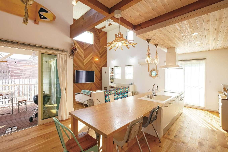 富士ホームズデザイン【デザイン住宅、輸入住宅、インテリア】開放感あふれる空間に、ヘリンボーンの壁やあえてラフに塗り上げられた天井がほっとするあたたかみを添えている。迫力あるオークのダイニングテーブルは、村松社長がとくに力を入れて用意したもの。味のある照明は直営のインテリアショップ『La Chouette Fuji』で吟味した