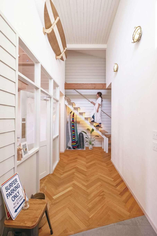 富士ホームズデザイン【デザイン住宅、輸入住宅、インテリア】ヘリンボーンの床へと段差なく続くフラットスタイルの玄関。外と同じ板張りの壁やストリートにあるショップのようなガラスの間仕切り、そしてマリンランプやサーフボードなどの装飾によって、ビーチサイドにある小さなホテルを思わせるオリジナルな空間に仕上がっている